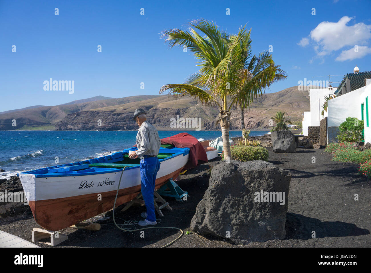 Old fisherman work on his boat at beach, fishing village Playa Quemada, Lanzarote island, Canary islands, Spain, Stock Photo