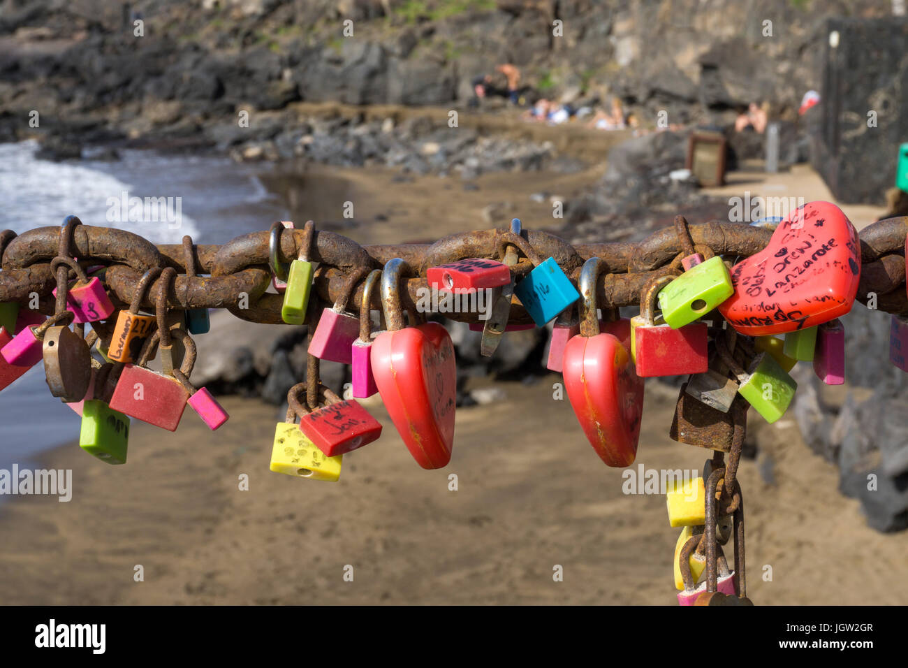 Love lockers hanging on chain at Playa Grande, large beach at Puerto del Carmen, Lanzarote island, Canary islands, - Stock Image