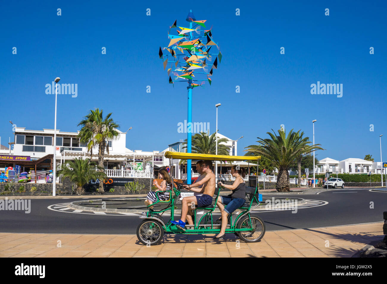 Tourists on 4-wheel biciyle at the colourful Wind chime 'El Robalo' of Cesar Manrique, Puerto del Carmen, - Stock Image