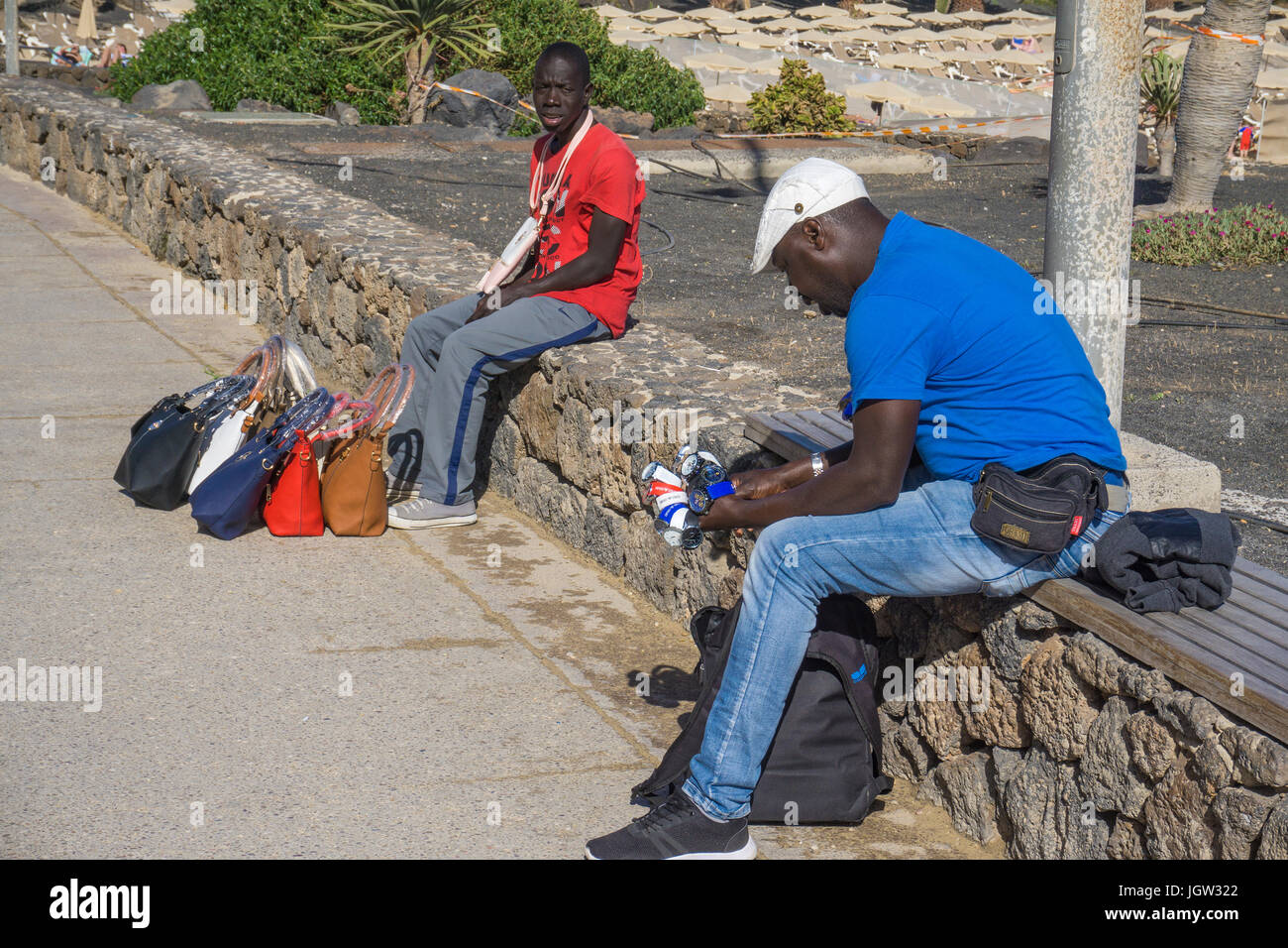 African street seller trying to sell handbags and watches at promenade Playa de las Cucharas, Costa Teguise, Lanzarote, - Stock Image