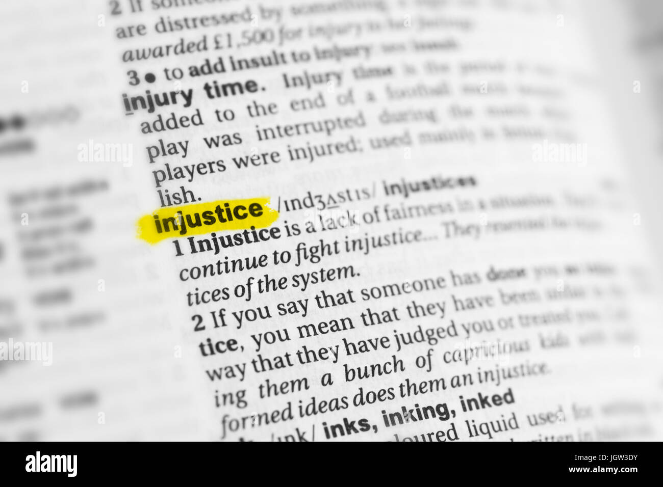 Highlighted English word 'injustice' and its definition at the dictionary. - Stock Image