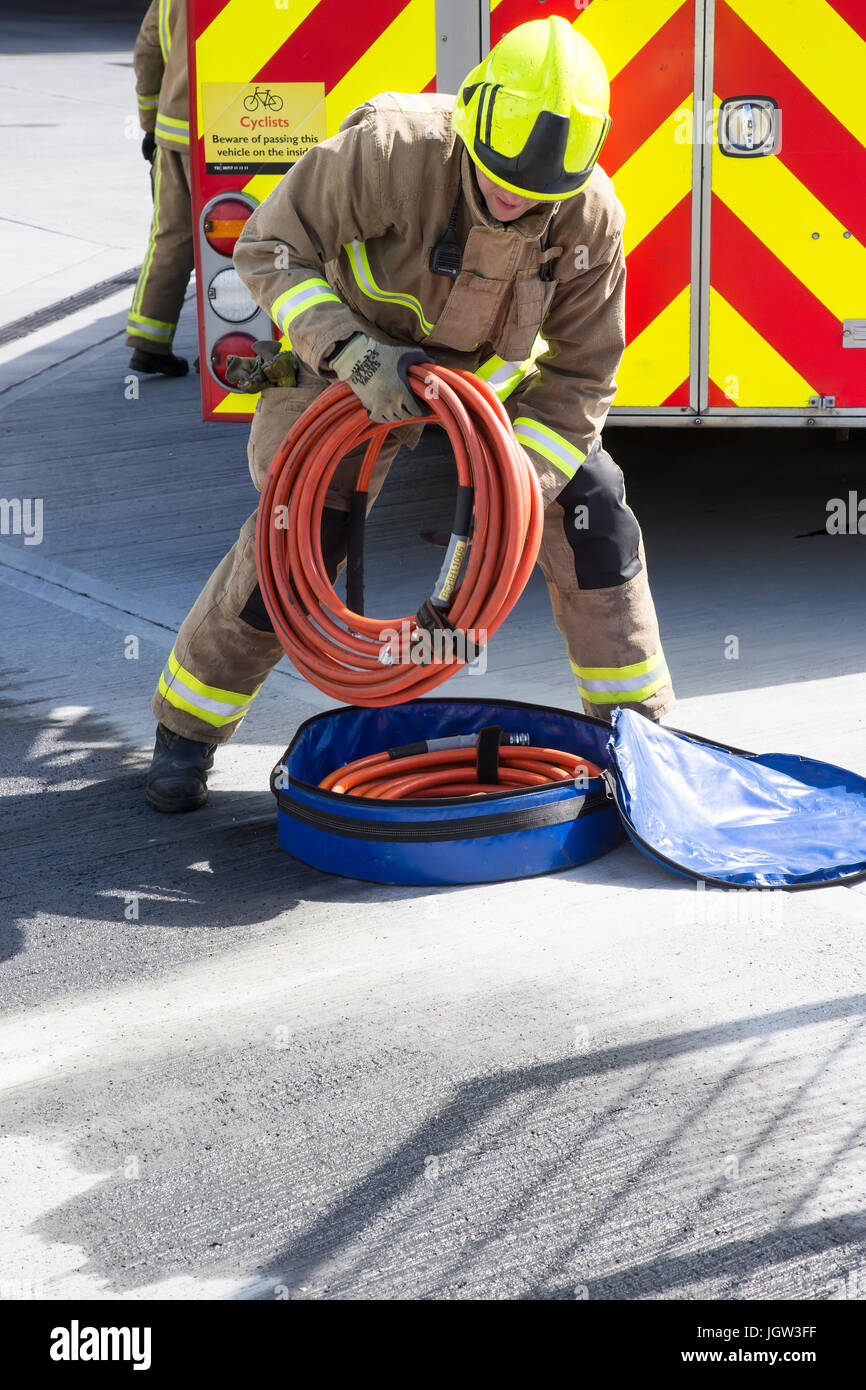 UK firefighter storing fire hose after use - Stock Image