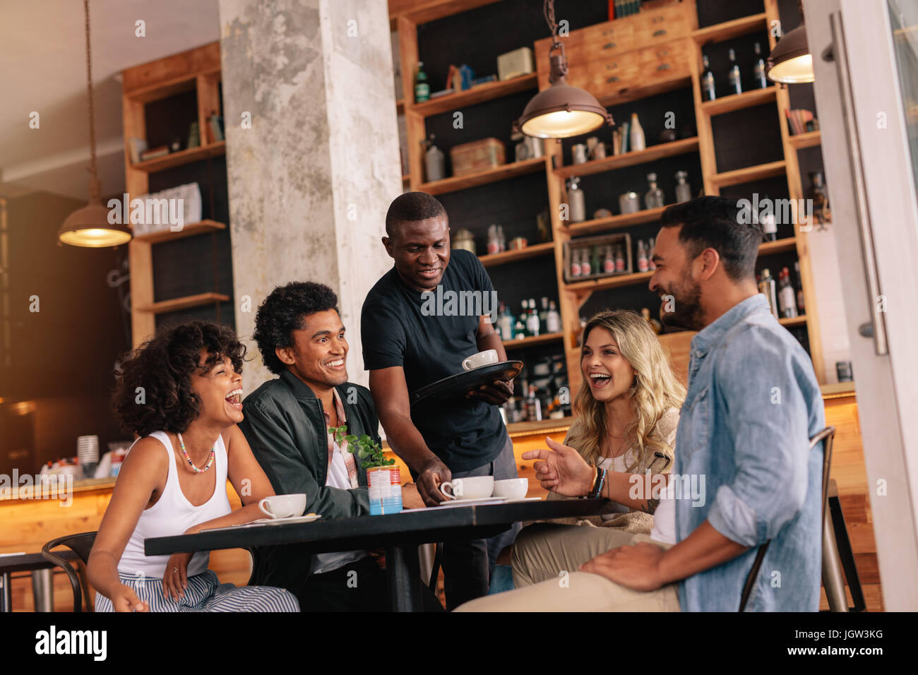 Group of friends sitting around table and waiter serving coffee at cafe. Young people meeting at coffee shop. - Stock Image