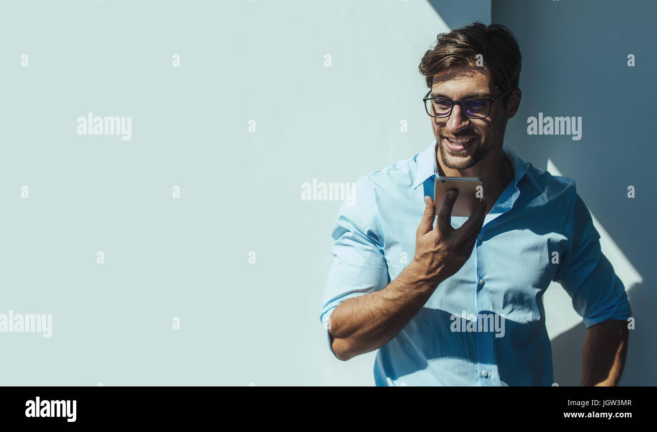 Businessman talking on speaker phone standing by a wall. Smiling young man with eyeglasses holding a mobile phone - Stock Image