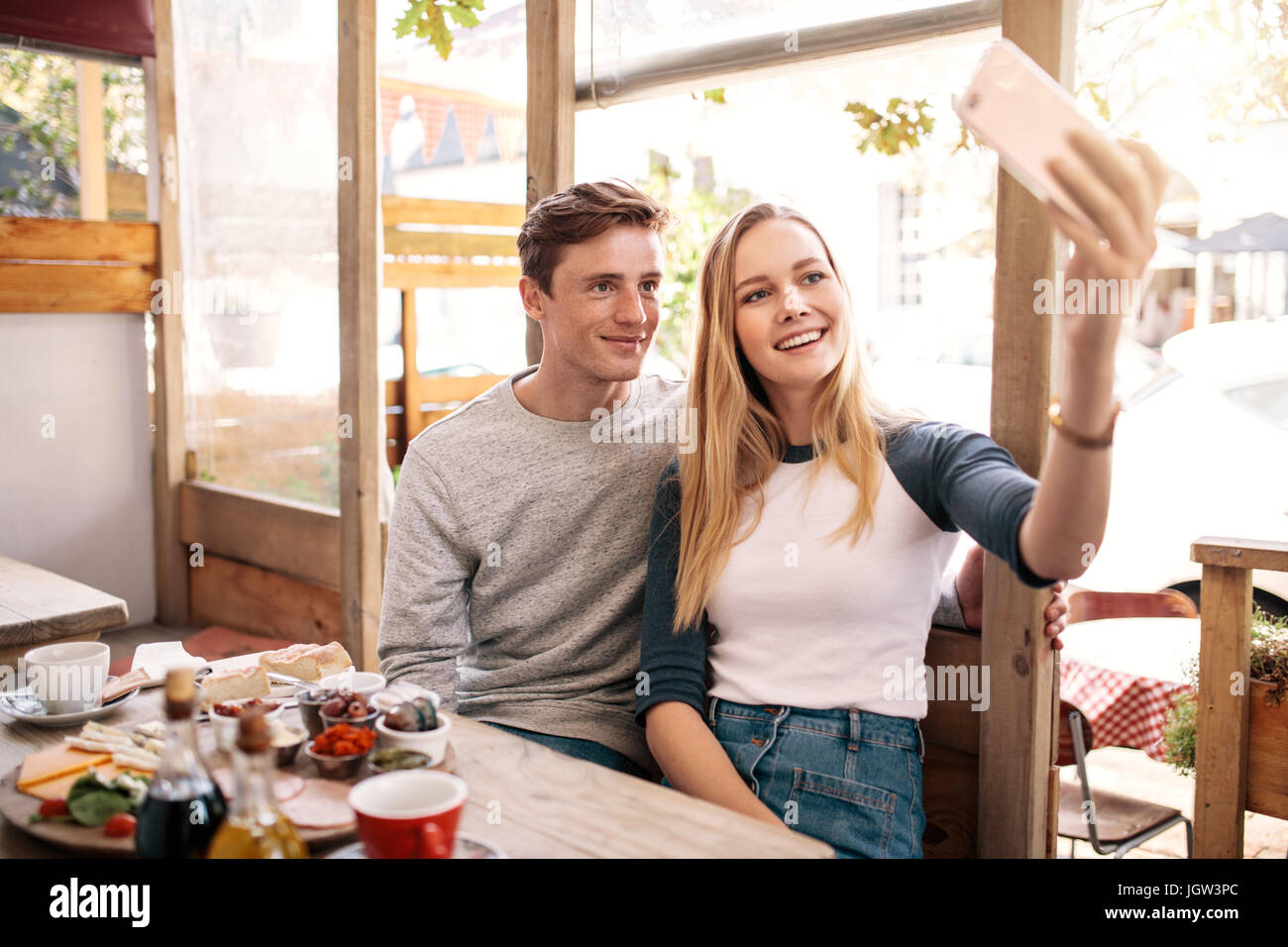Couple taking photos of themselves with mobile phone in cafe. Stylish young couple catching memories by smart phone. - Stock Image