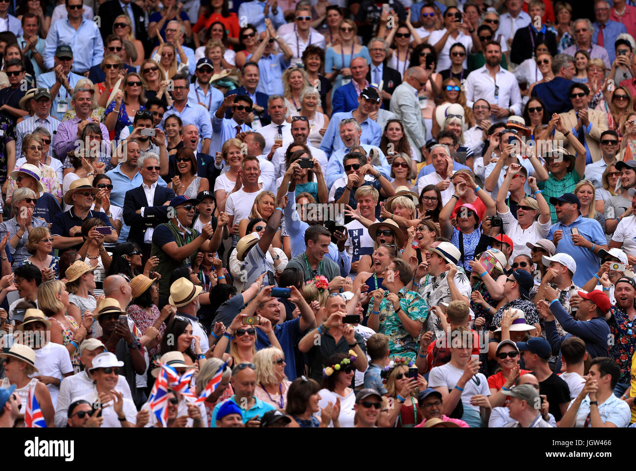 Spectators compete for the wristband of Andy Murray after he throws it into the crowd on day seven of the Wimbledon Stock Photo