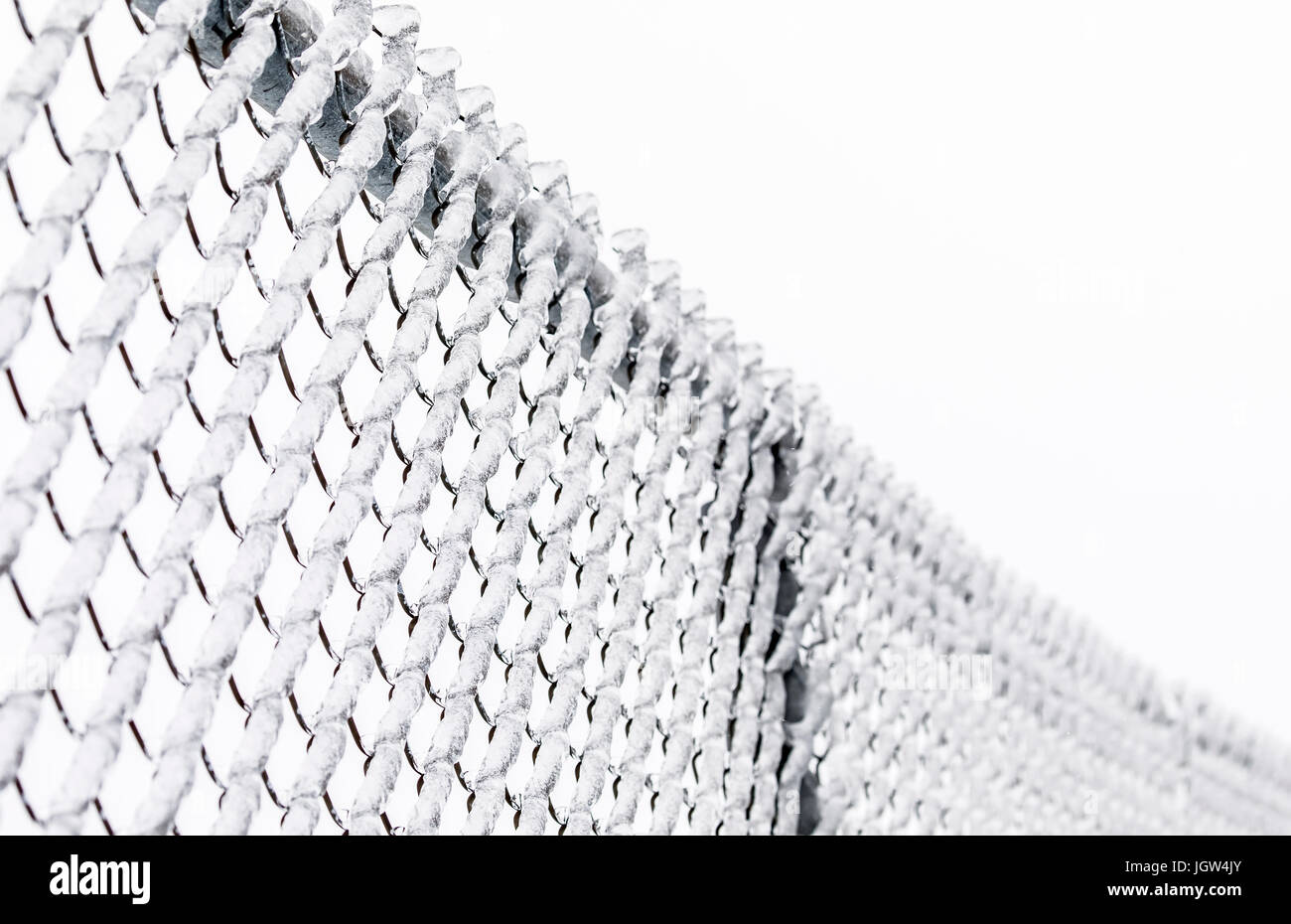 Chain-link fence covered in ice. - Stock Image