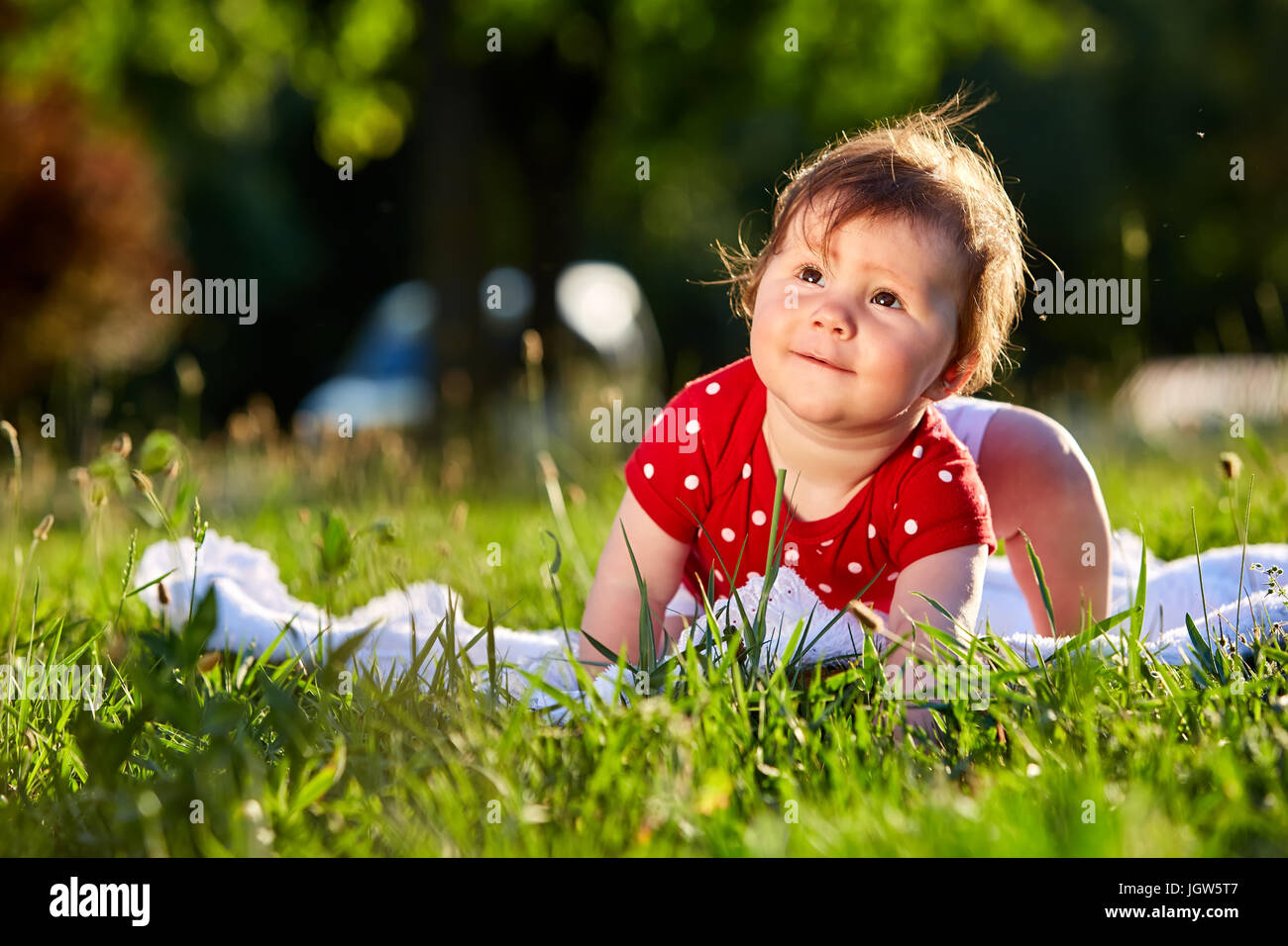 Image of: Pictures Cute Adorable Nice Baby Girl In Red Spring Dress Smiling Sitting Under The Tree Baby Sitting On Grass In The Park Alamy Cute Adorable Nice Baby Girl In Red Spring Dress Smiling Sitting