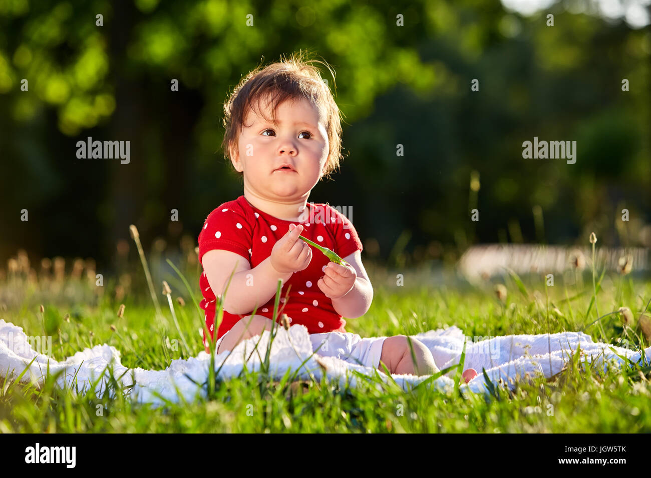 Image of: Desktop Cute Adorable Nice Baby Girl In Red Spring Dress Smiling Sitting Under The Tree Baby Sitting On Grass In The Park Alamy Cute Adorable Nice Baby Girl In Red Spring Dress Smiling Sitting