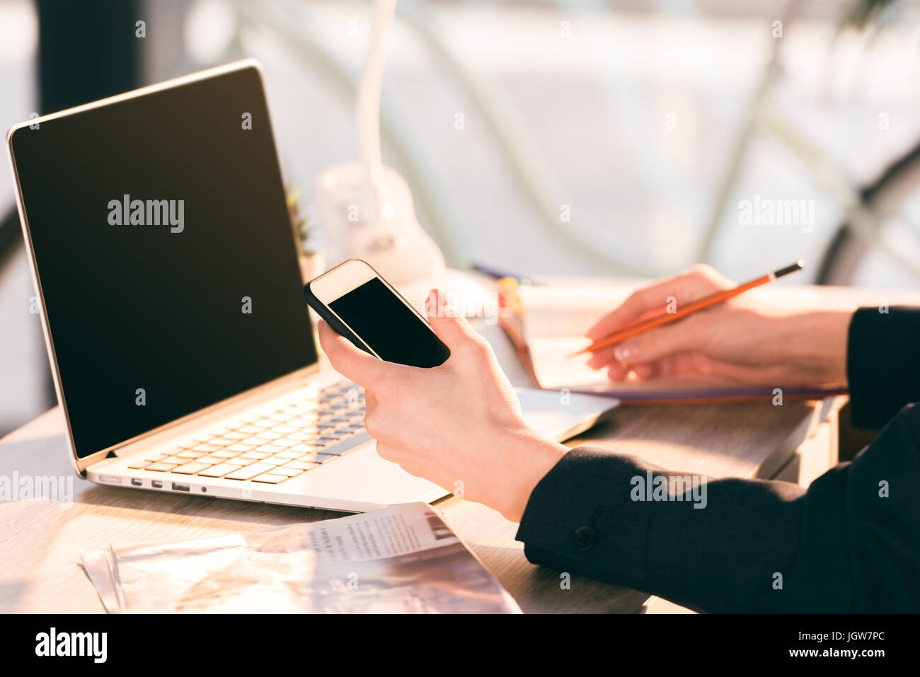 Close-up partial view of businesswoman using laptop and smartphone with blank screens - Stock Image