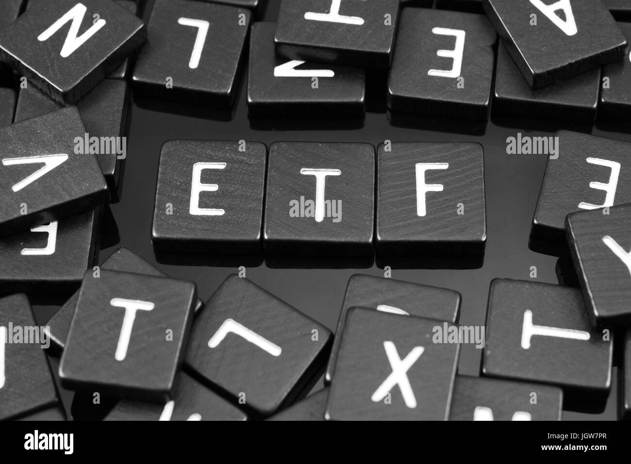 """Black letter tiles spelling the word """"etf"""" on a reflective background Stock Photo"""