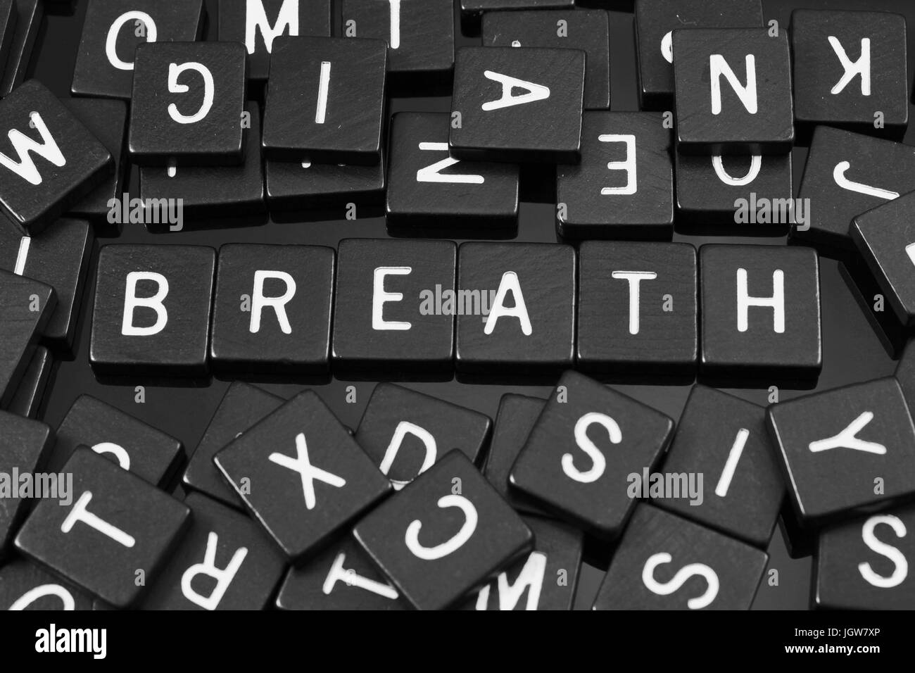 Black letter tiles spelling the word 'breath' on a reflective background - Stock Image