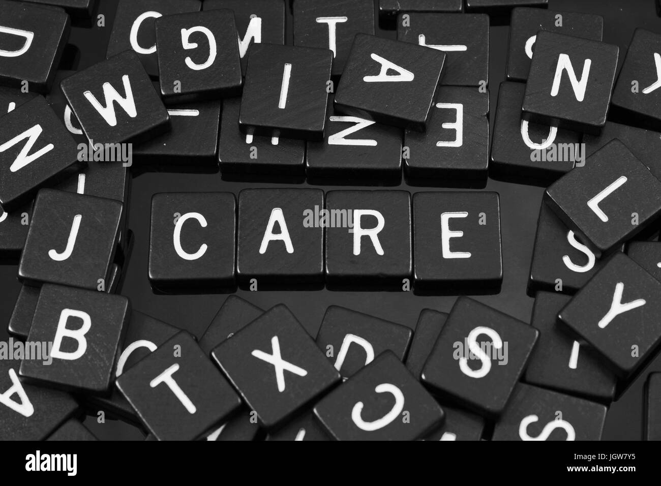 Black letter tiles spelling the word 'care' on a reflective background - Stock Image