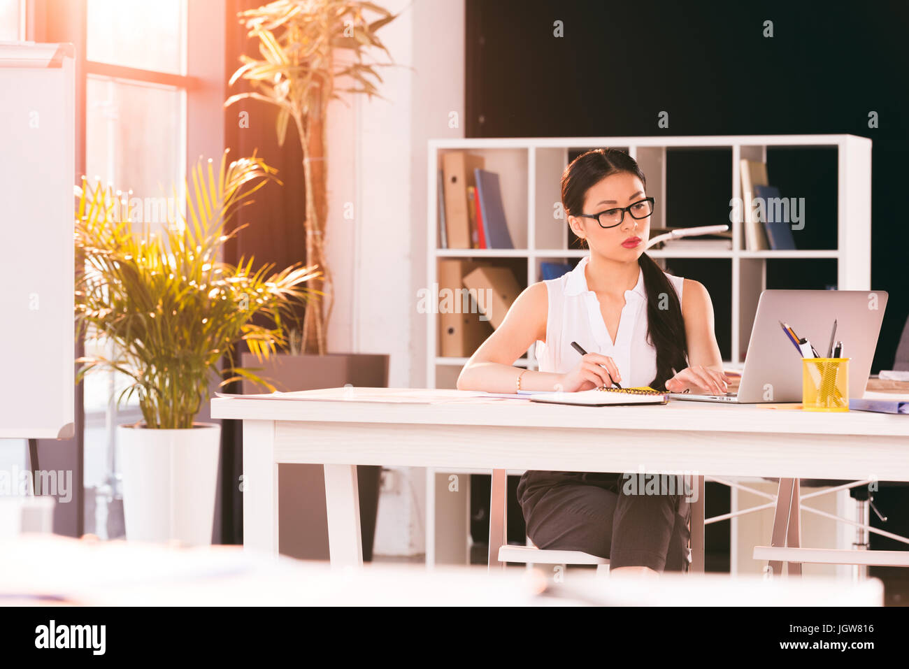 pensive asian businesswoman sitting at workplace and working in modern office - Stock Image