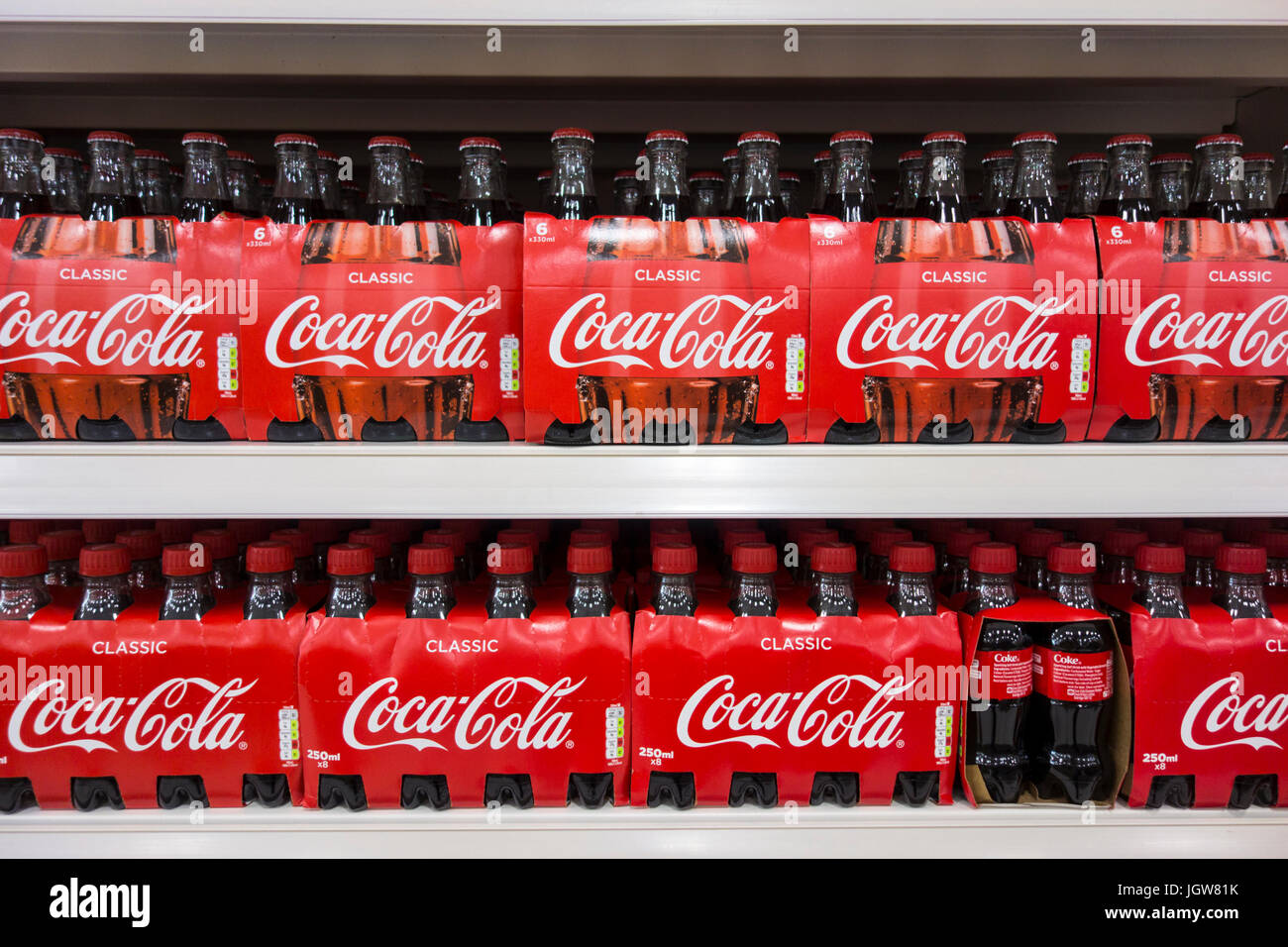 Multi-pack glass and plastic bottles of Coca Cola / Coke for sale on a supermarket shelf in the UK - Stock Image