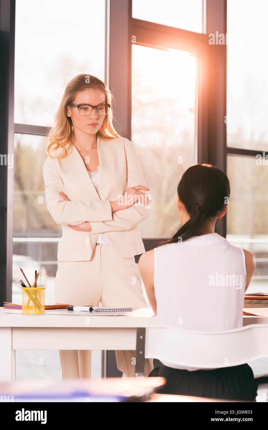 young businesswomen in formalwear talking at interview in modern office - Stock Image