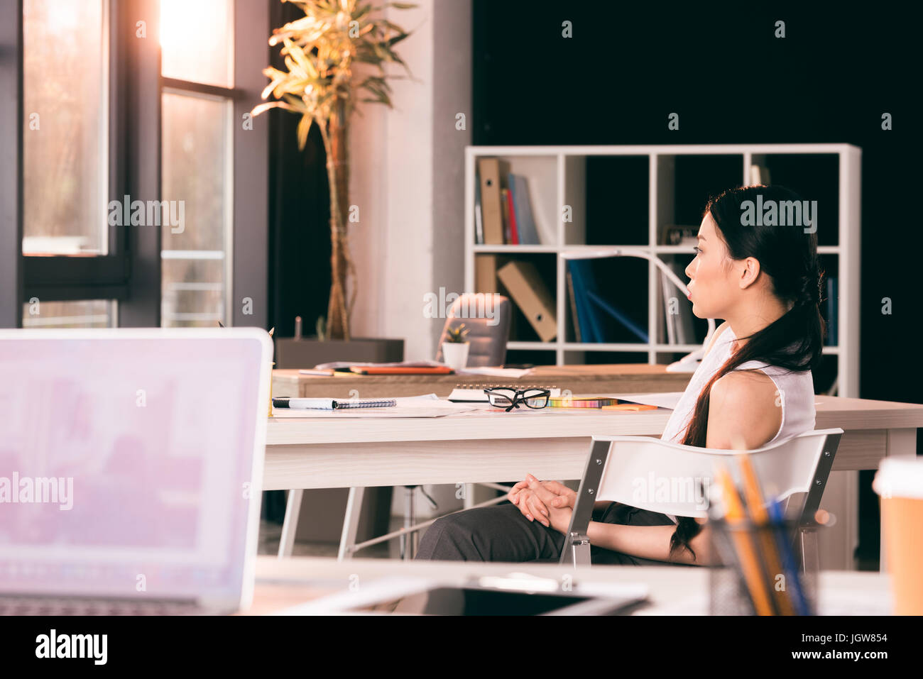 young asian businesswoman sitting at table in office and looking aside - Stock Image