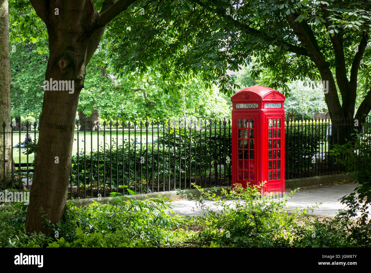Traditional Telephone Box outside Brunswick Square Gardens, London, UK - Stock Image