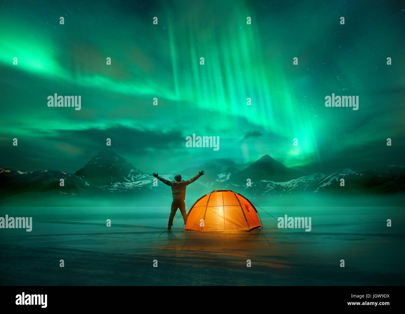 A man camping in wild northern mountains with an illuminated tent viewing a spectacular green northern lights aurora - Stock Image
