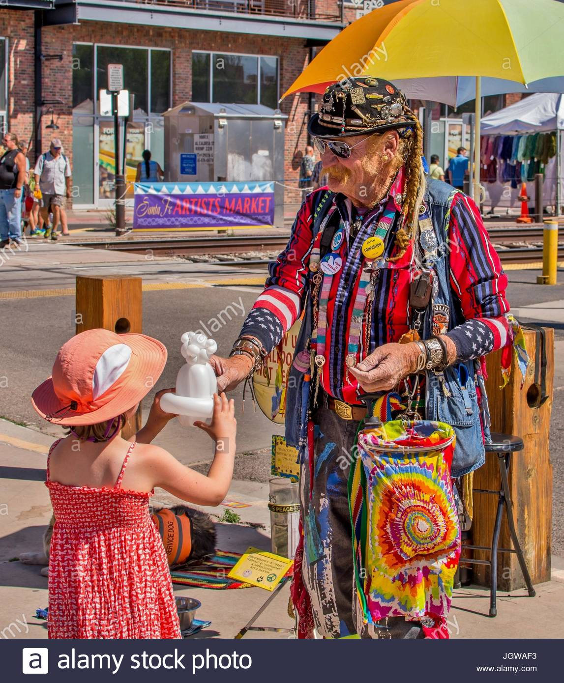 A balloon artist in colorful tie-dyed clothing makes an animal for a small girl in a hat at the Farmers' Market - Stock Image