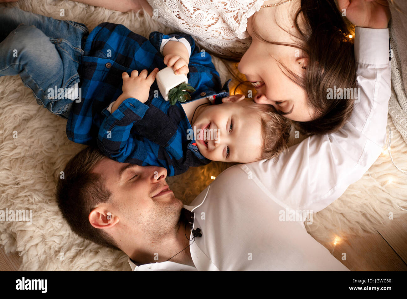 Happy young family lie on bed together. They laugh fun. Top view. Closeup. Stock Photo