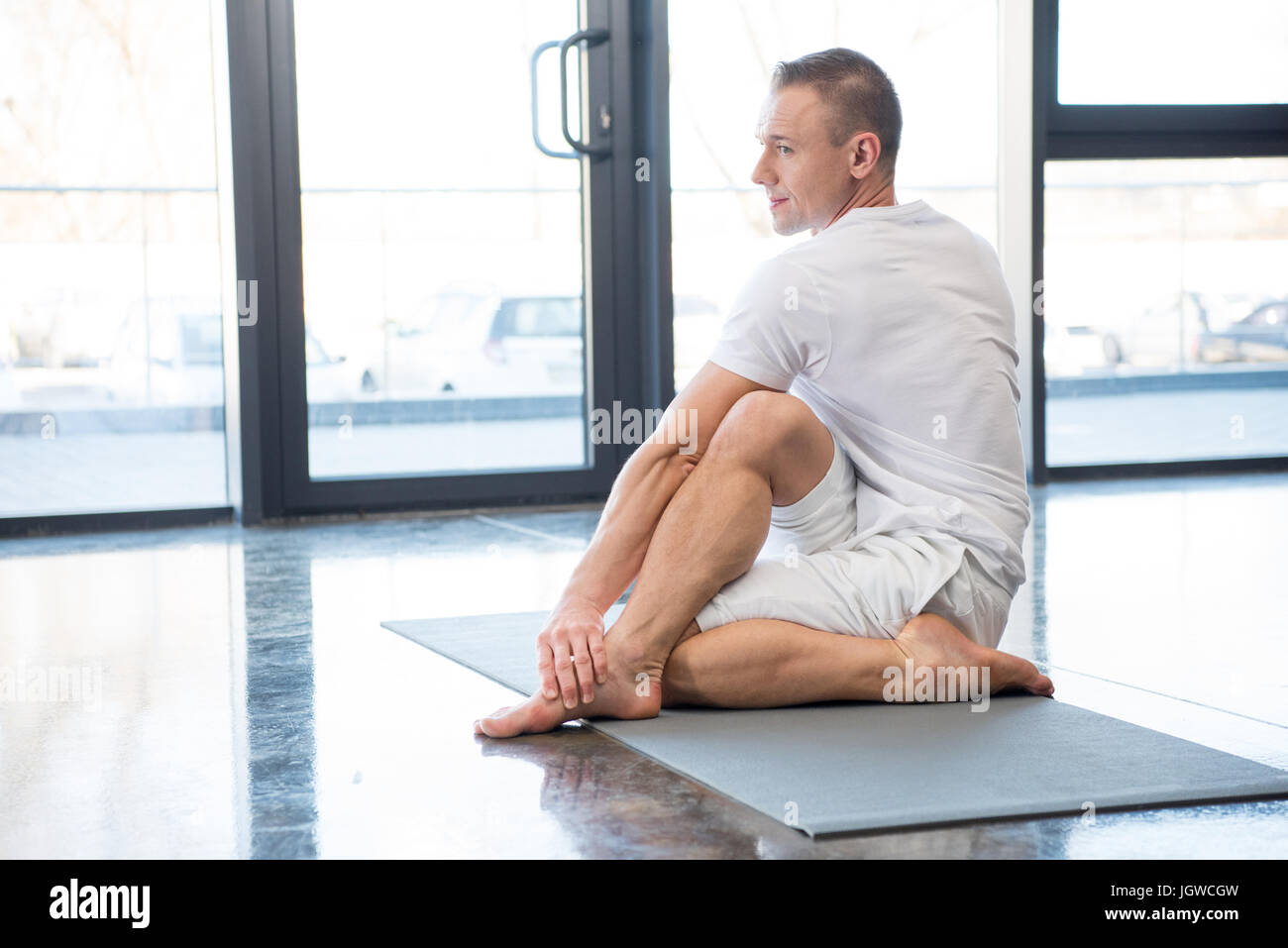 sportsman in half spinal twist pose sitting on yoga mat in gym - Stock Image