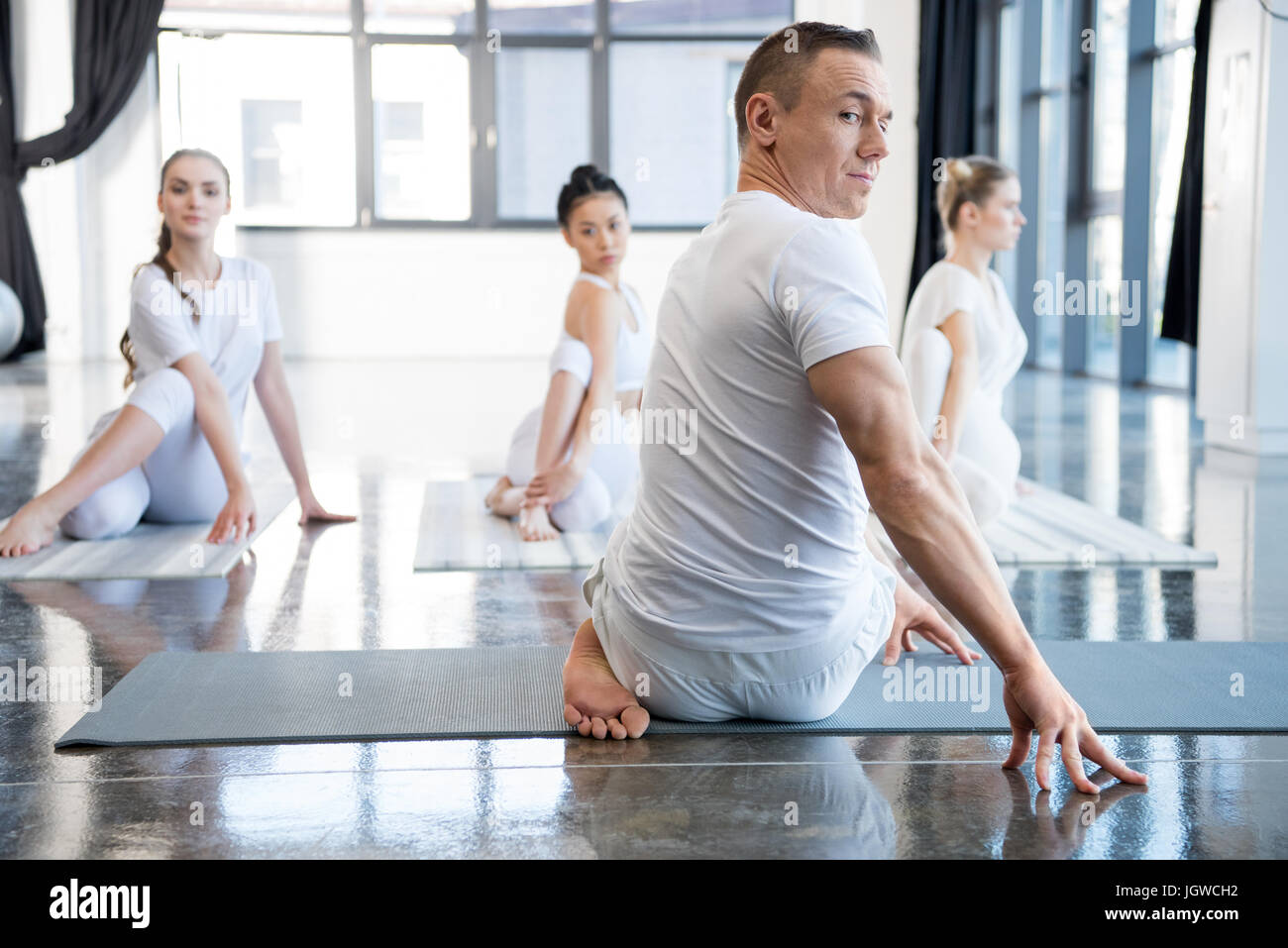 yoga trainer and his group practicing half spinal twist pose in gym - Stock Image