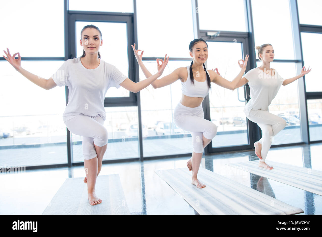 Smiling young women practising Garudasana Eagle Pose at yoga class - Stock Image
