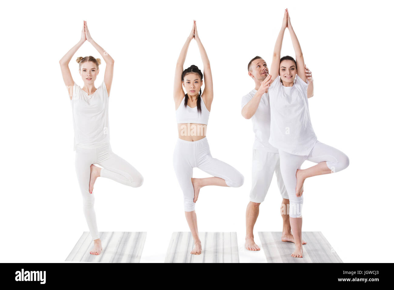 Trainer helping young women practicing yoga tree pose indoors Stock Photo