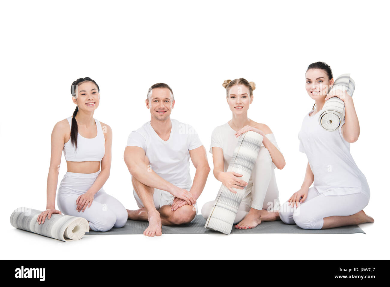 Group of smiling young women with trainer sitting together with yoga mats isolated on white - Stock Image