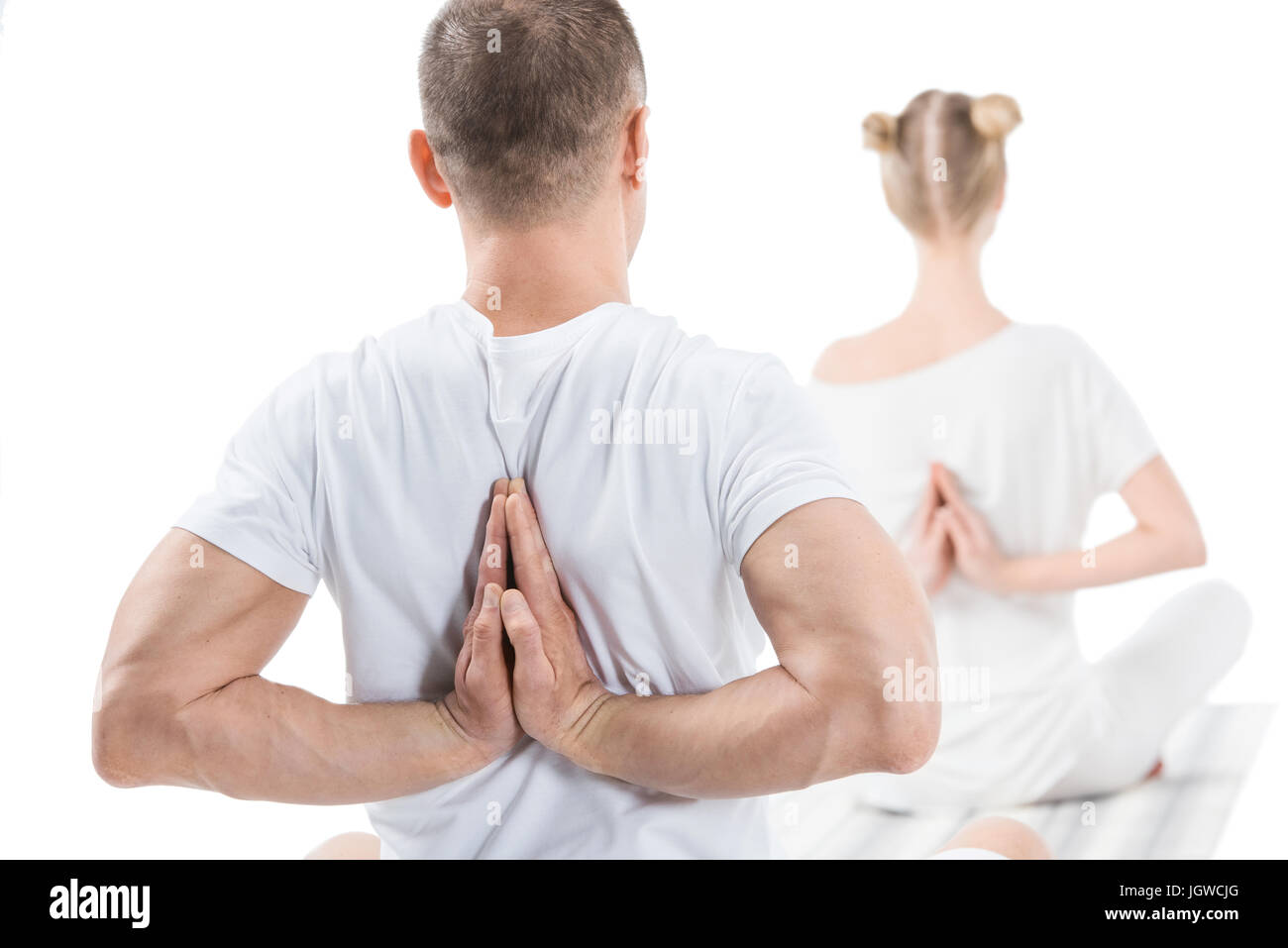 Back view of sporty young people sitting in lotus position with namaste mudra sign - Stock Image
