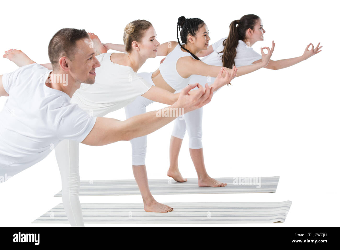 Side view of group of young women with trainer standing in Natarajasana yoga pose - Stock Image