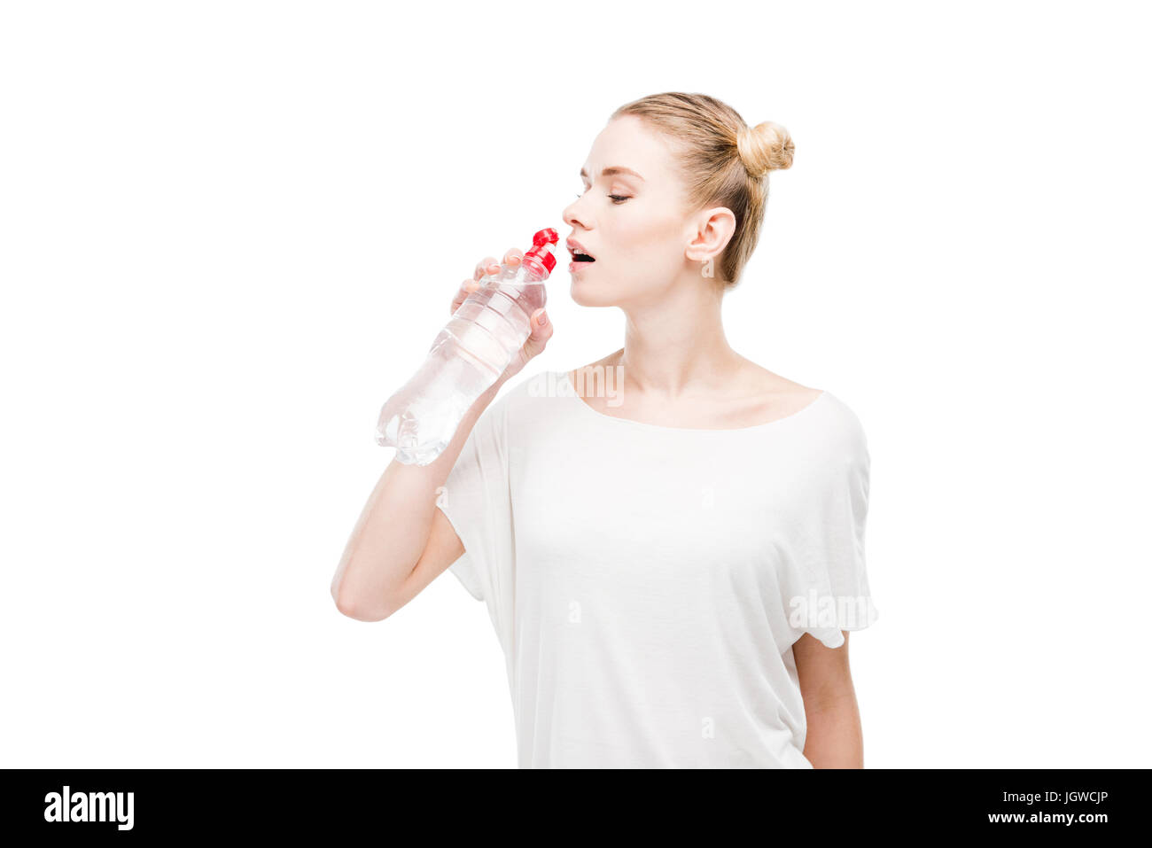 Attractive young woman in white t-shirt drinking water from bottle isolated on white - Stock Image