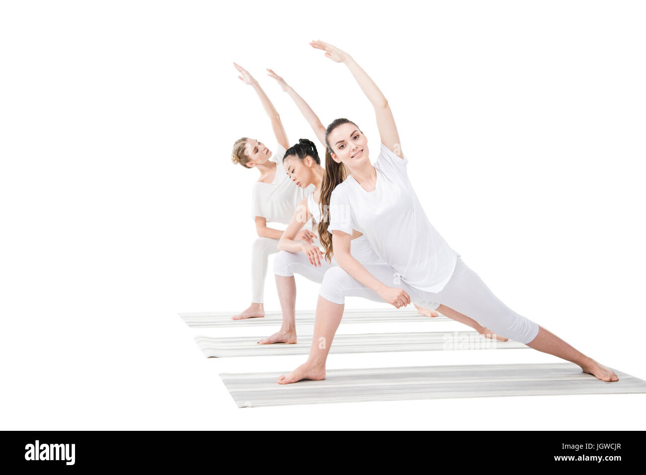 Smiling young women practicing Extended Side Angle Pose on yoga mats - Stock Image