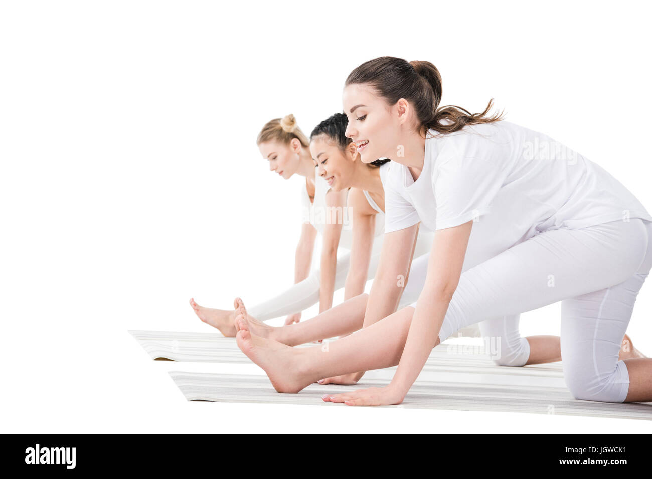Side view of young women in sportswear practicing yoga isolated on white - Stock Image