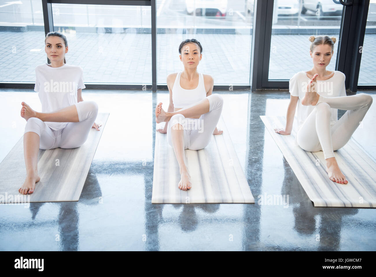 Concentrated young women performing yoga position together on yoga mats - Stock Image