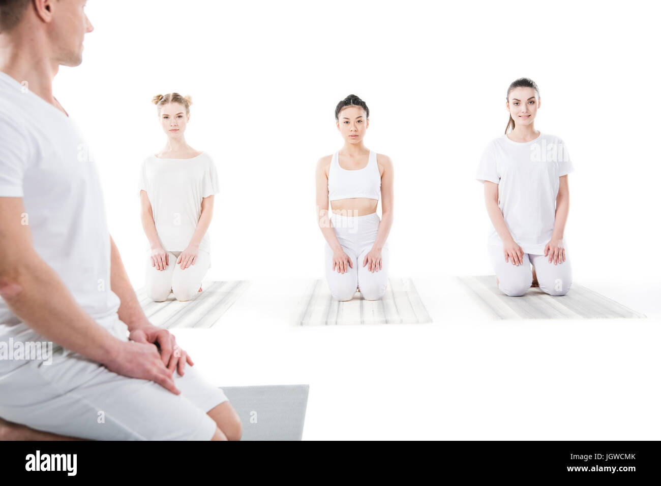 women sitting in Vajrasana pose on yoga mats with trainer isolated on white - Stock Image