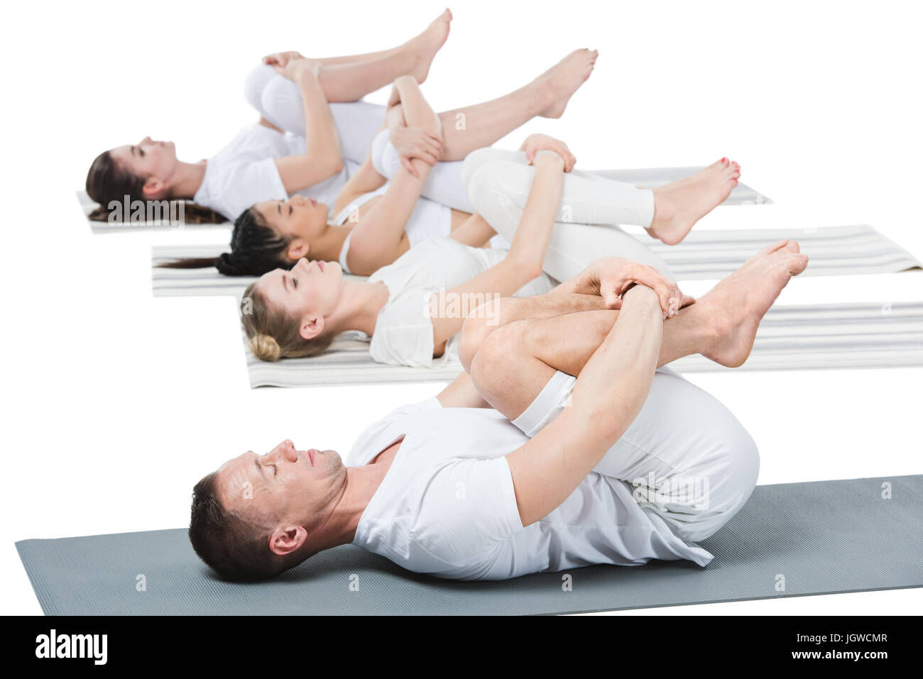 side view of people practicing yoga on yoga mats isolated on white - Stock Image