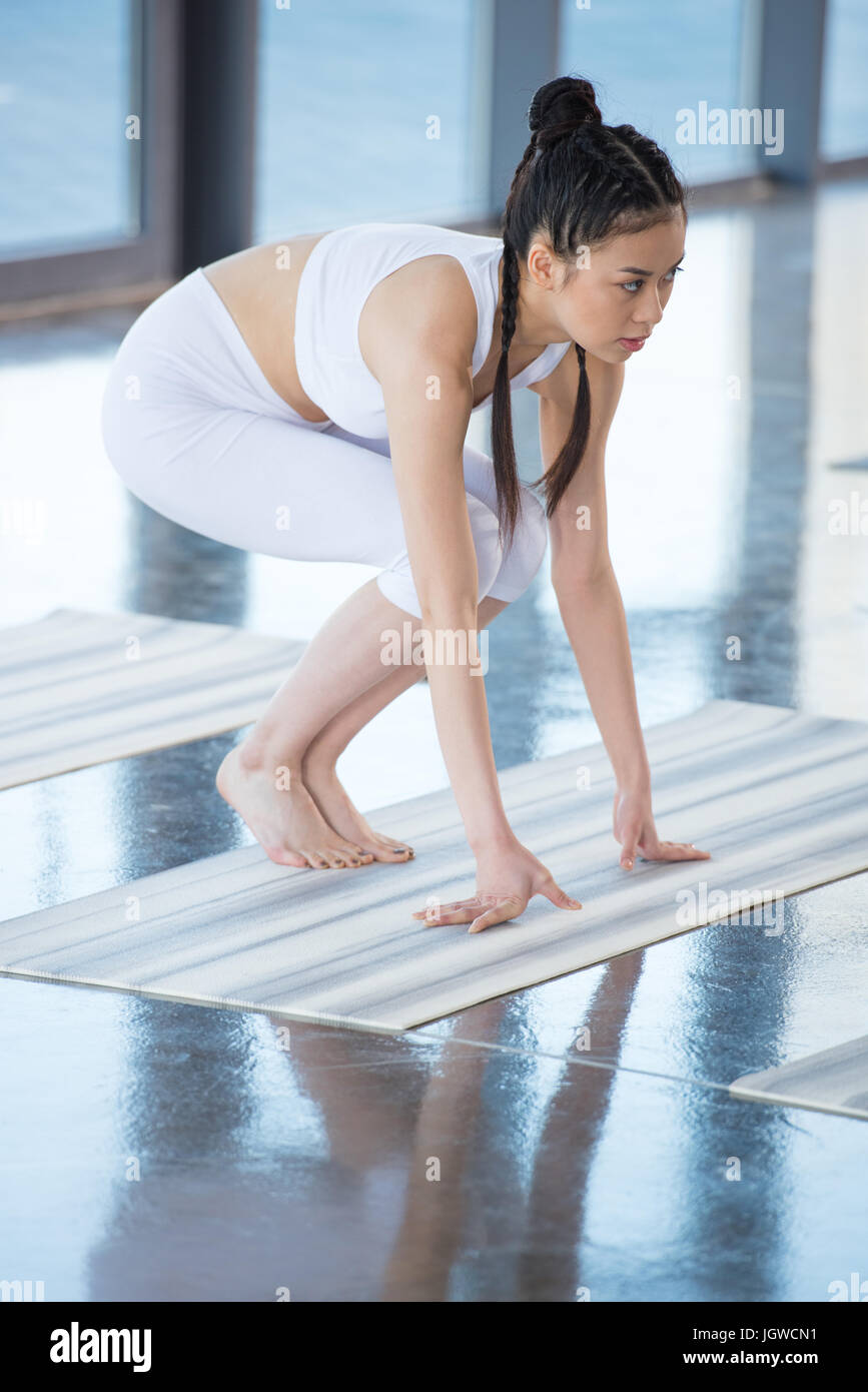 side view of asian woman practicing crane pose on yoga pose - Stock Image