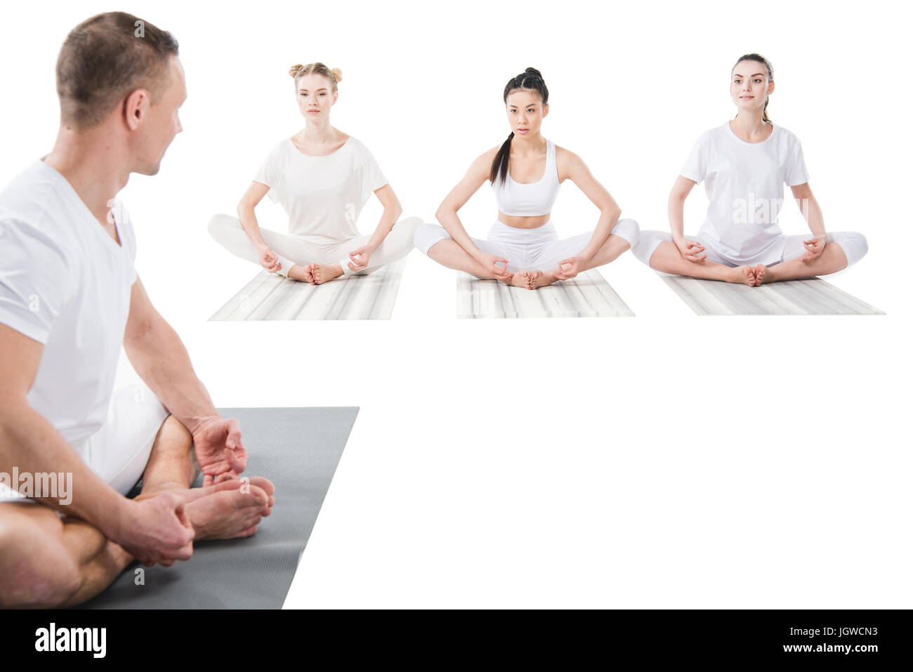 trainer helping women doing yoga pose isolated on white - Stock Image