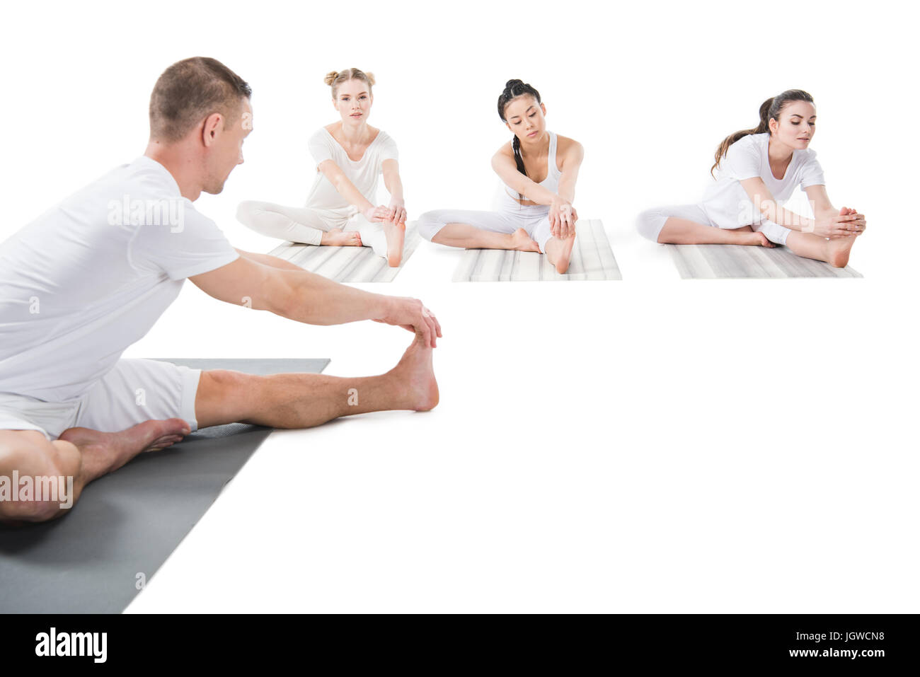 man and women practicing yoga together on yoga mats isolated on white - Stock Image