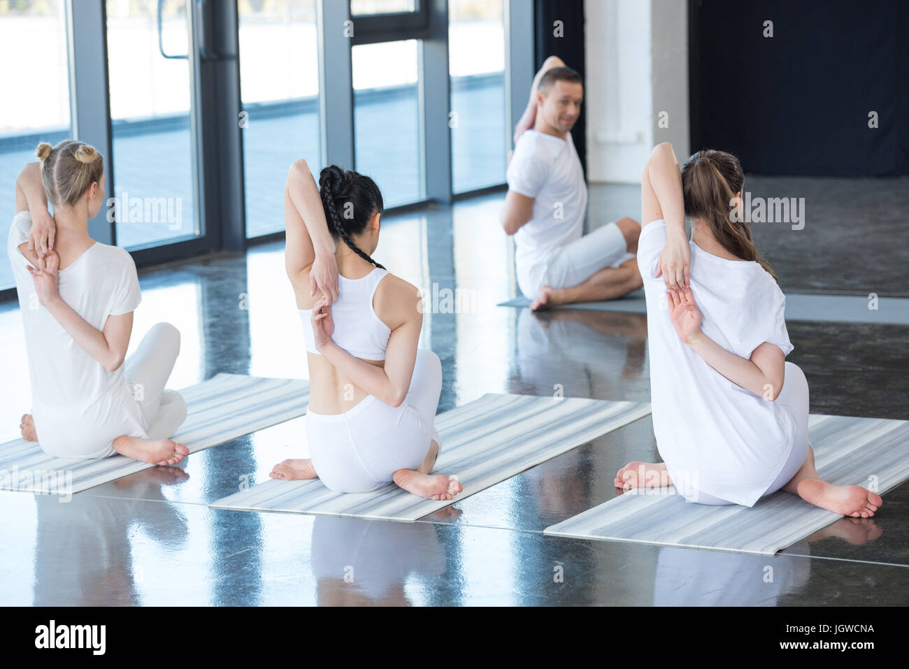 women and trainer performing Gomukhasana or Cow face pose on yoga mats - Stock Image