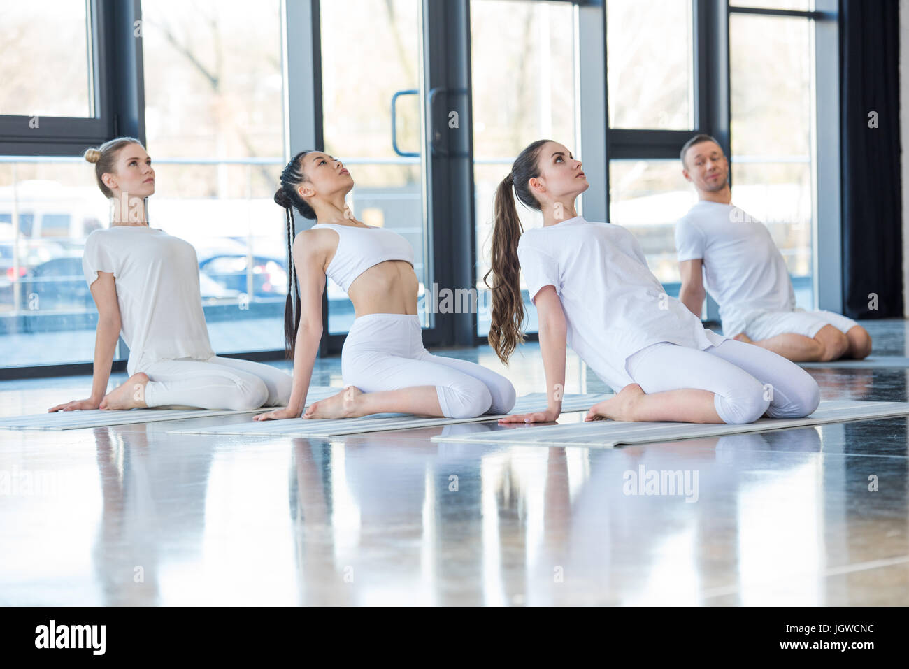 side view of group of women practicing yoga on mats together with trainer - Stock Image