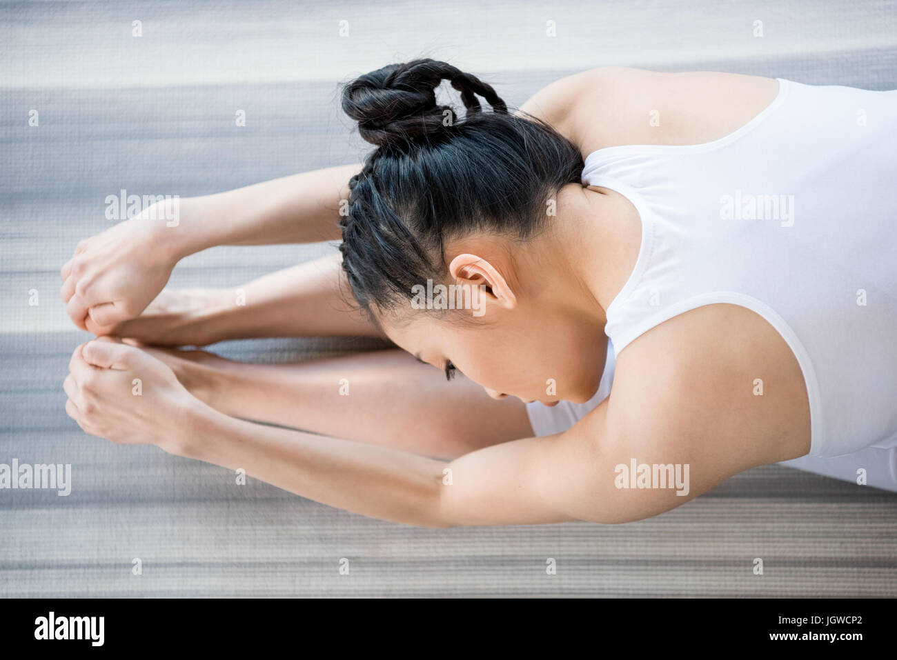 young woman practicing Yoga in forward bending pose - Stock Image