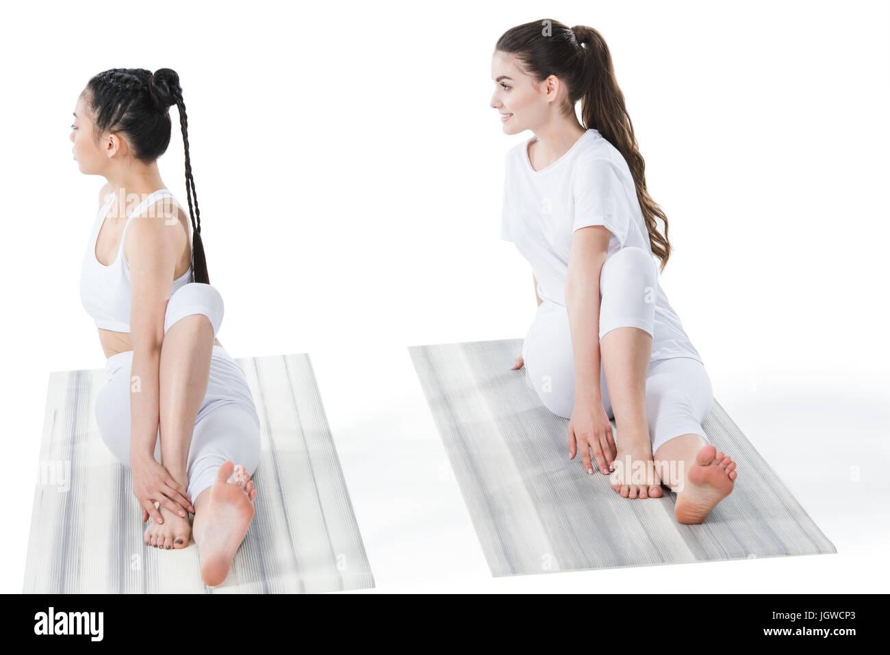 multiethnic young women doing twisting sage pose (Marichyasana) isolated on white - Stock Image