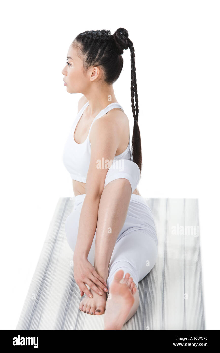 young asian woman practicing yoga in twisting sage pose (Marichyasana) on yoga mat Stock Photo