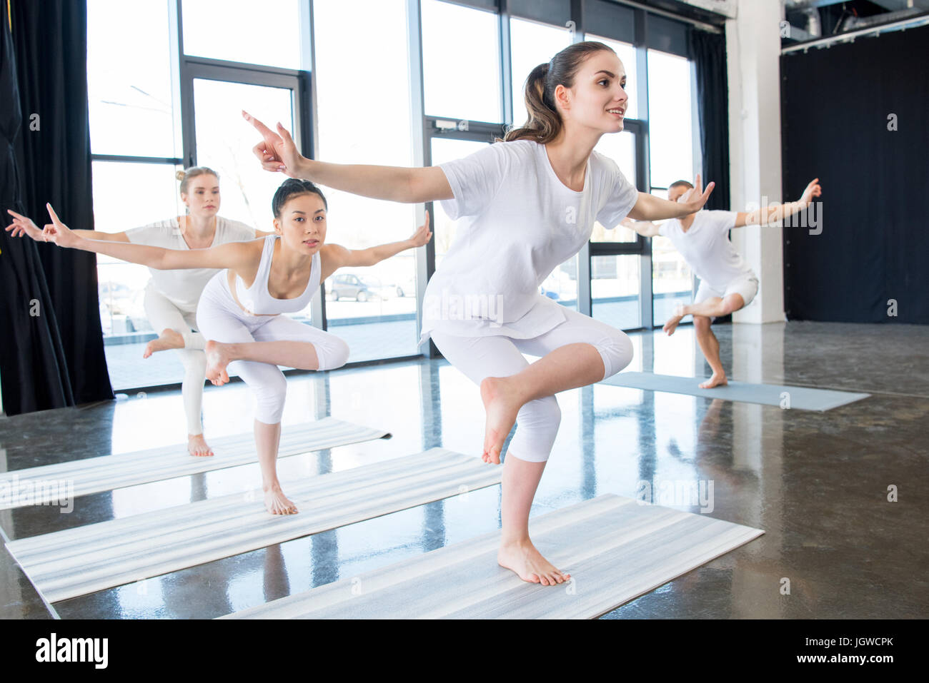 girls doing Golden Rooster Stands on One Leg yoga Stance with instructor indoors - Stock Image