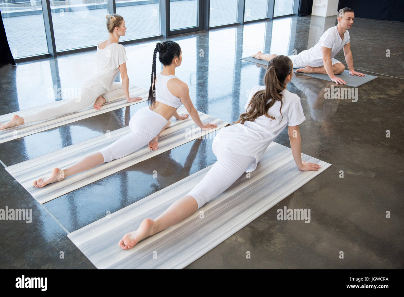 multiethnic women doing Half-Pigeon position with instructor indoors - Stock Image