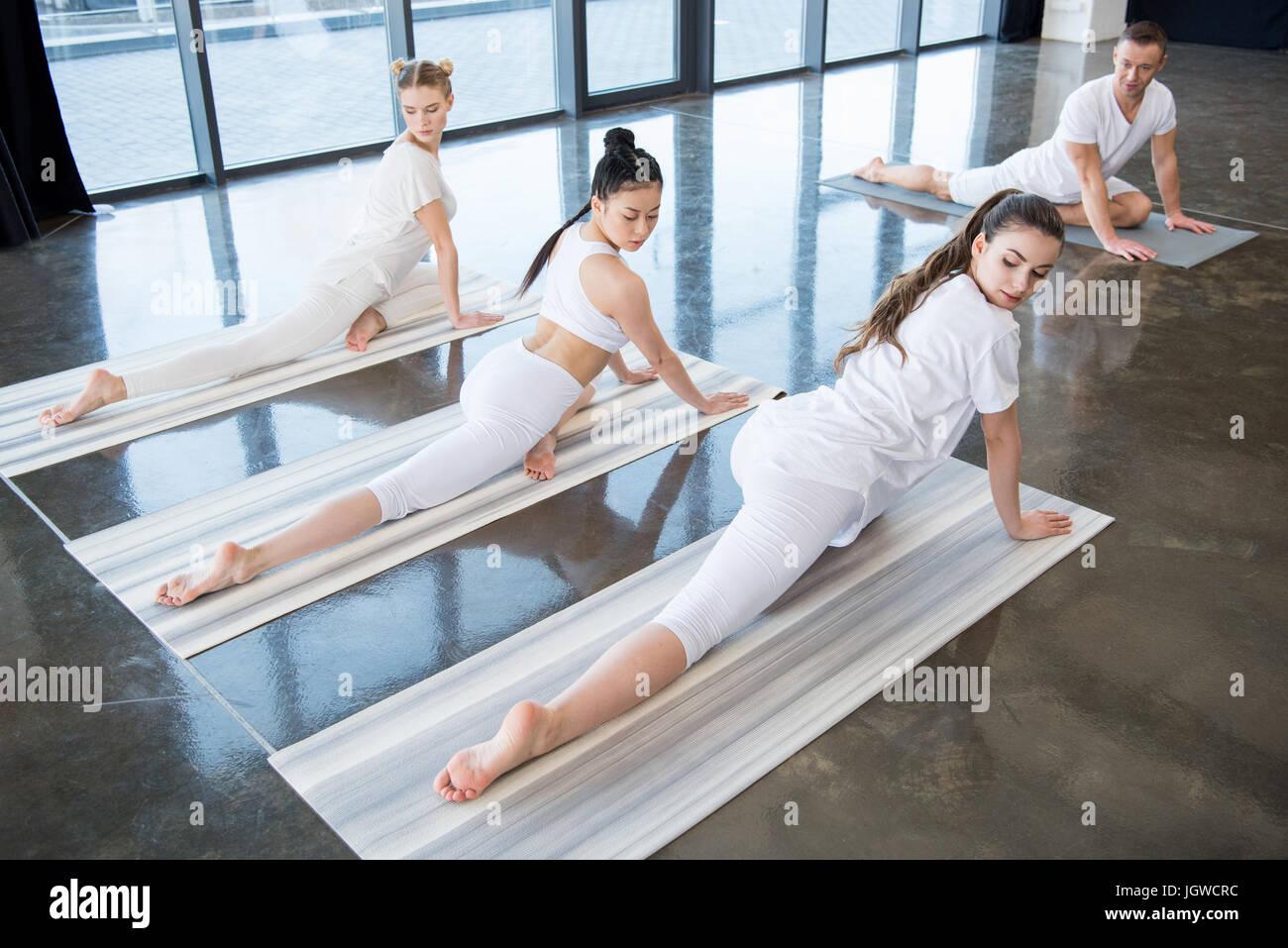 multiethnic girls doing Half-Pigeon yoga pose with instructor indoors - Stock Image