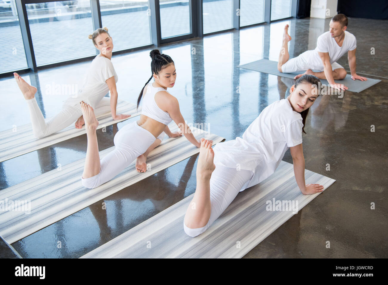 young women doing Half King Pigeon asana with instructor indoors - Stock Image